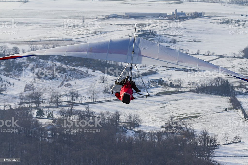 Hang Glider Soaring High Over Snowy Farm Fields royalty-free stock photo