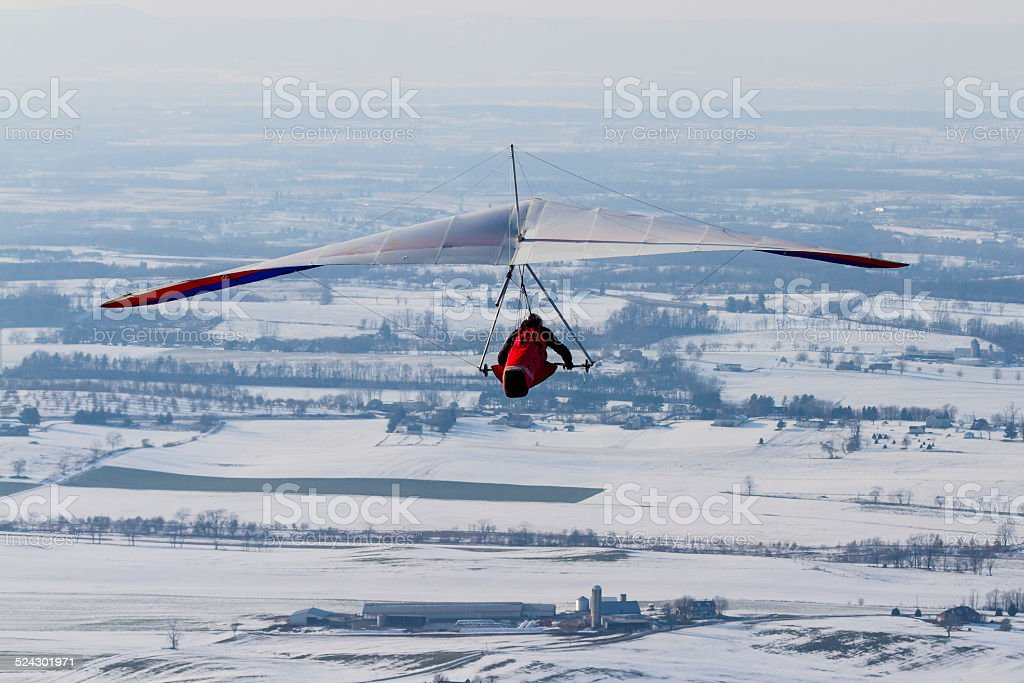Hang Glider Soaring High Over Snowy Farm Fields stock photo