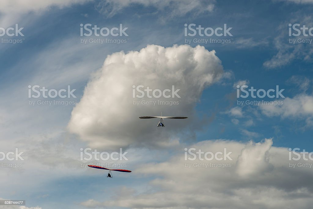 Hang gliders soar high above clouds stock photo