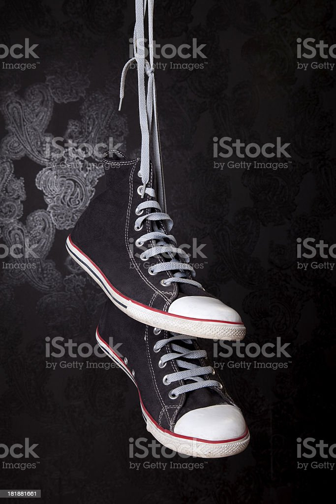 Hanged black sneakers on wallpaper royalty-free stock photo