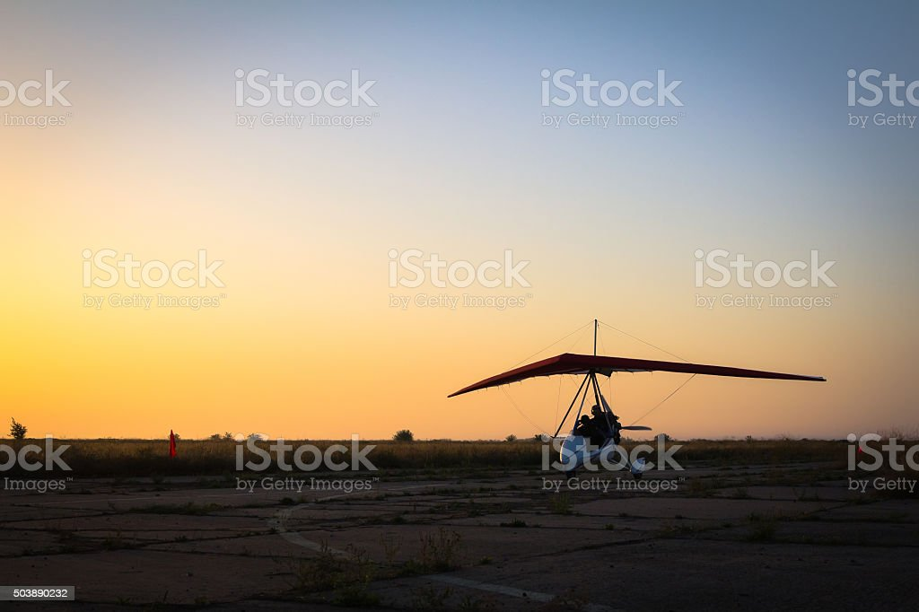Hang-gliding, standing at dawn on the runway stock photo