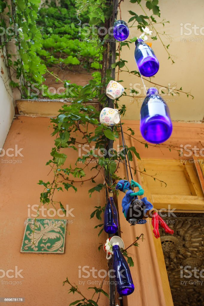 Hanging blue bottles near wall with green plant stock photo