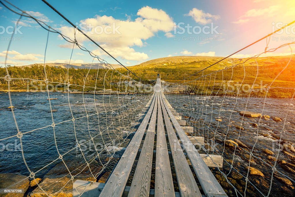 hanging bridge over mountain river stock photo
