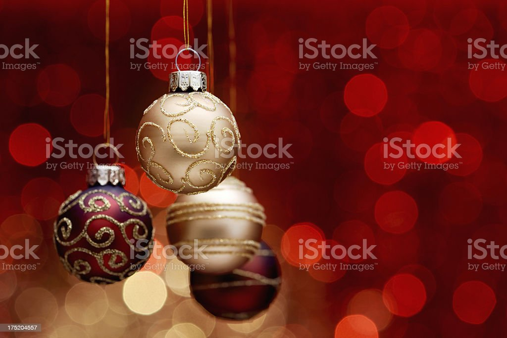 Hanging christmas balls on gold-red illuminated background royalty-free stock photo