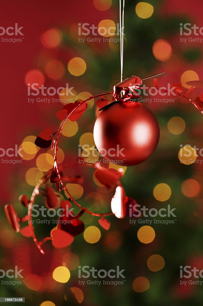 Hanging christmas bauble infront of christmas-tree royalty-free stock photo