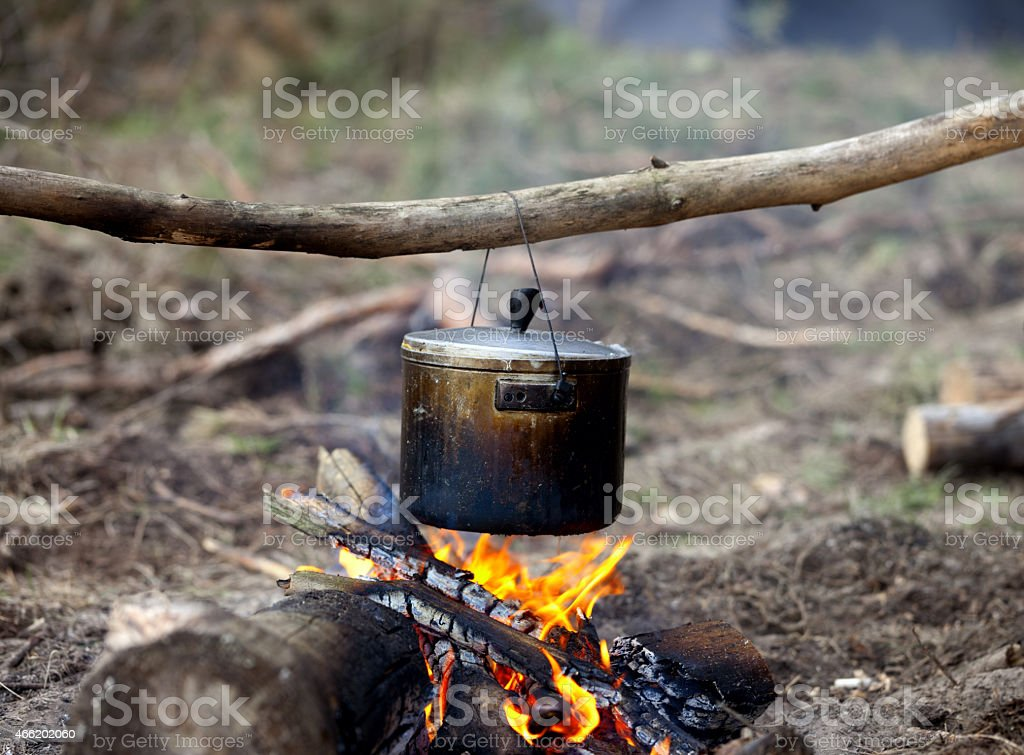 Hanging cooking pot over bonfire stock photo