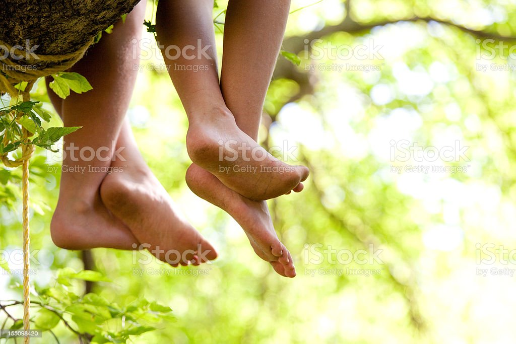 Hanging Feet From Children Sitting in Tree stock photo