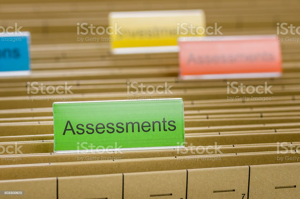 Hanging file folder labeled with Assessments stock photo