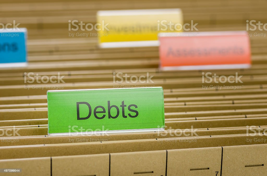 Hanging file folder labeled with Debts stock photo