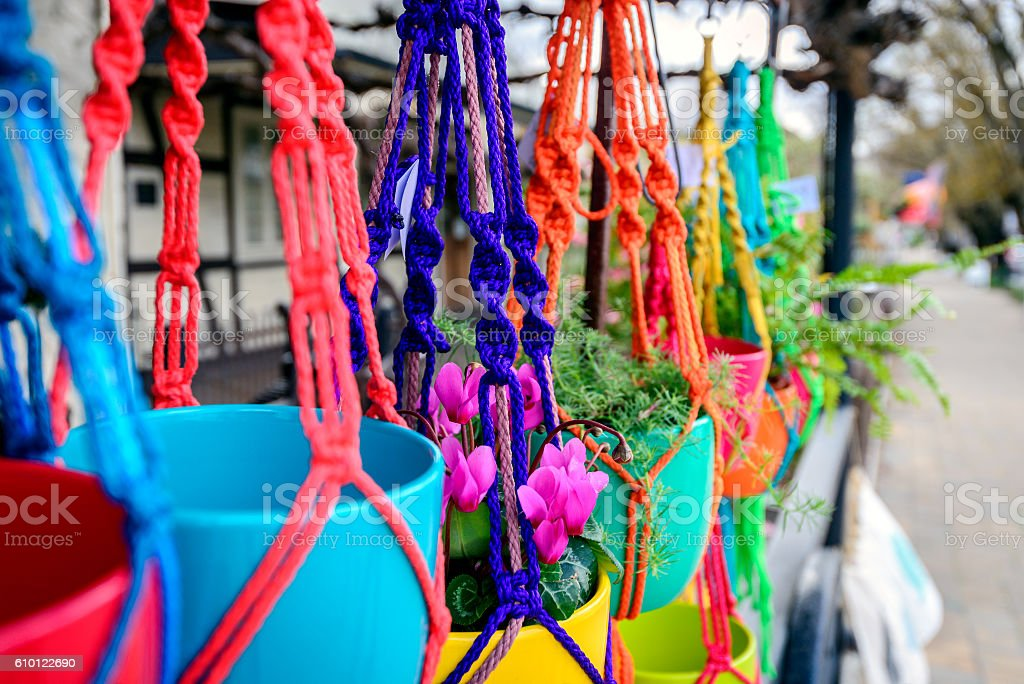 Hanging flowers in colorful pots stock photo