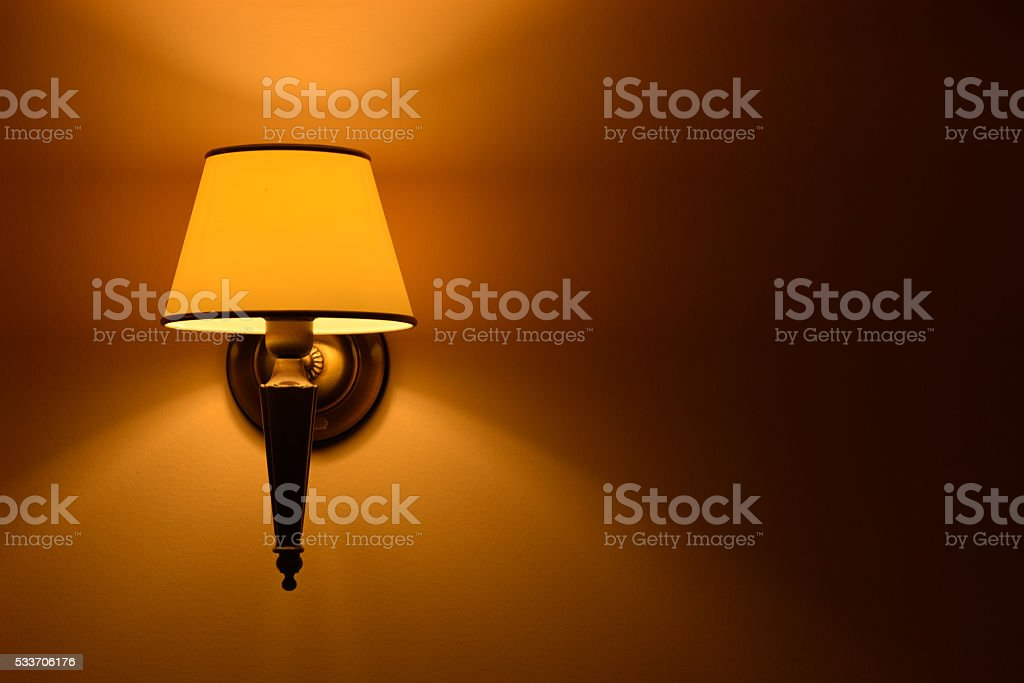 Hanging lamp lit wall in natural light stock photo