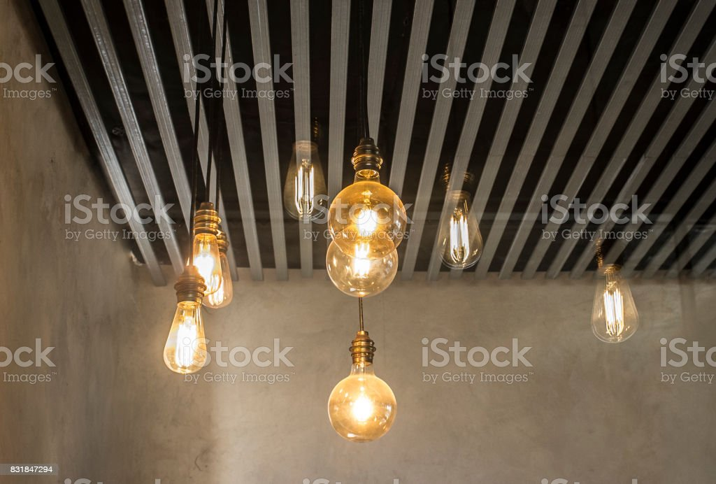 Hanging light bulbs over grey dark strip ceiling stock photo