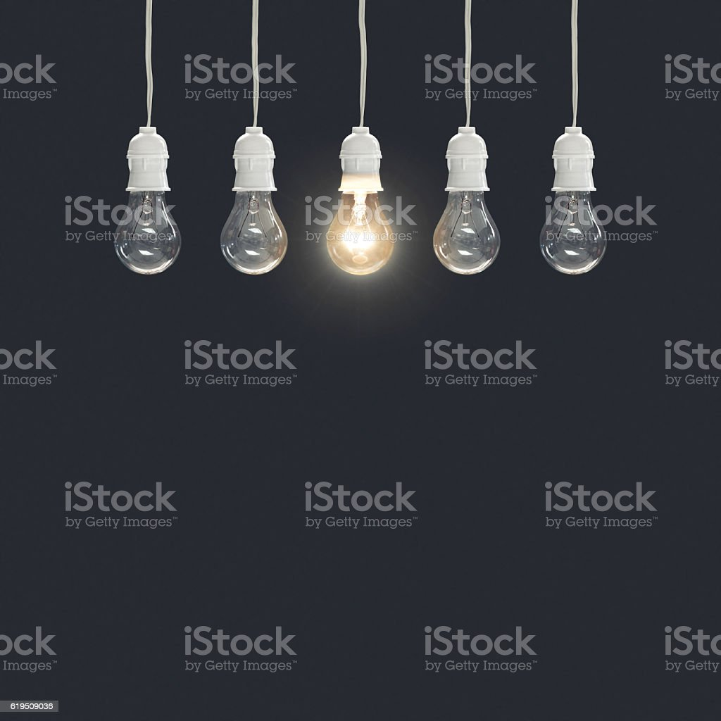 Hanging light bulbs with glowing one stock photo