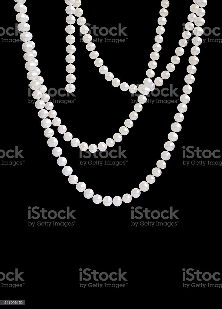 Hanging natural pearl necklace, isolated on black stock photo