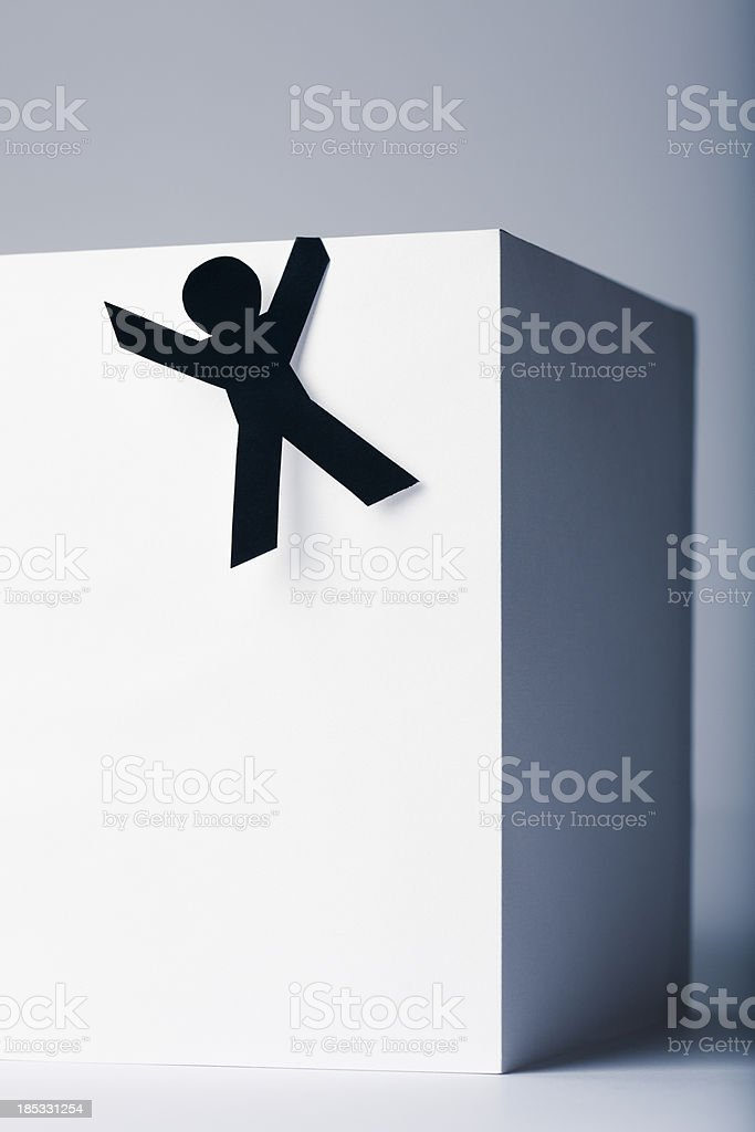 Hanging off the edge - paper people concept stock photo