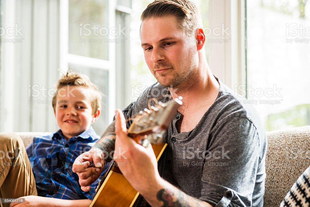 Hanging out with dad playing guitar. stock photo