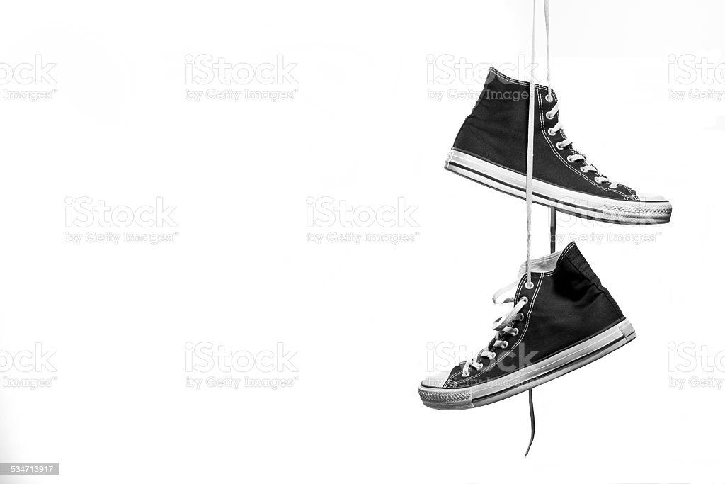 Hanging Pair of Black and White Sneakers stock photo
