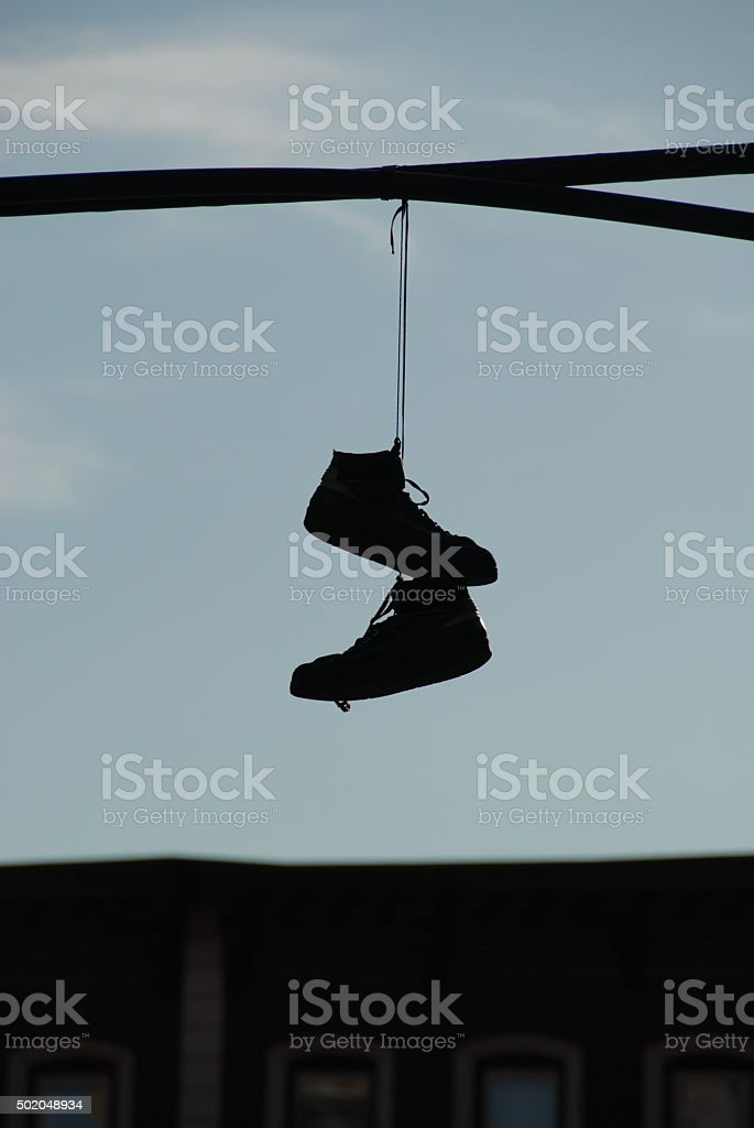 Hanging pair of shoes on a wire stock photo