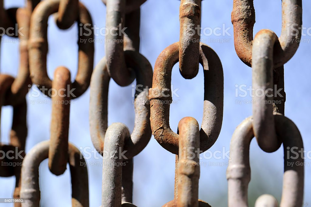 Hanging rusty chain on blue sky background. stock photo