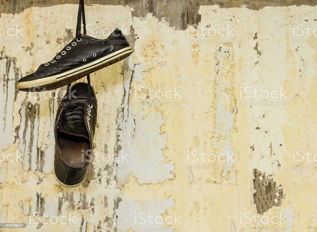 hanging shoe on stone background. stock photo