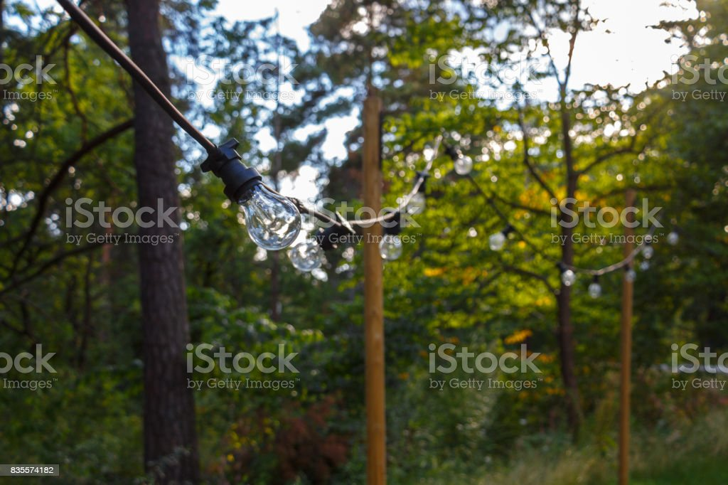 hanging strand of old fashion incandescent light bulbs on black electrical wire strung outside stock photo