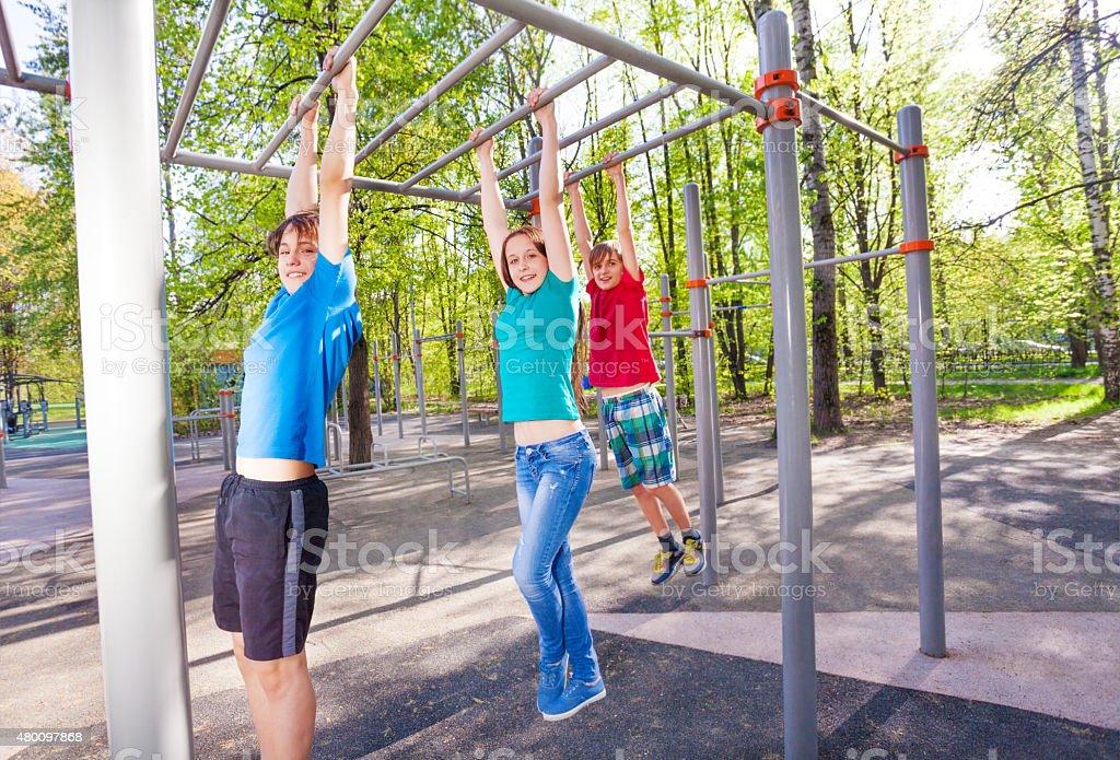 Hanging teenagers on the brachiating bar stock photo