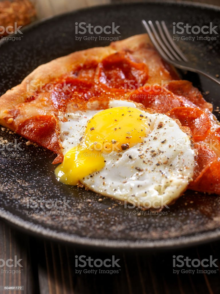 Hangover Breakfast,Leftover Pizza with a Fried Egg stock photo