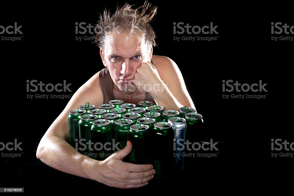 Hangover.The drunk man and is  lot of empty beer cans stock photo