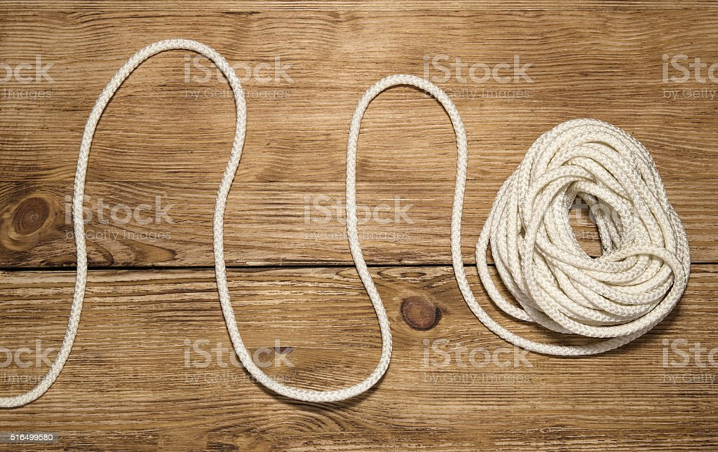 Hank of white rope on the wooden background stock photo