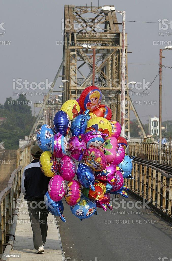 Hanoi balloon seller on landmark bridge stock photo