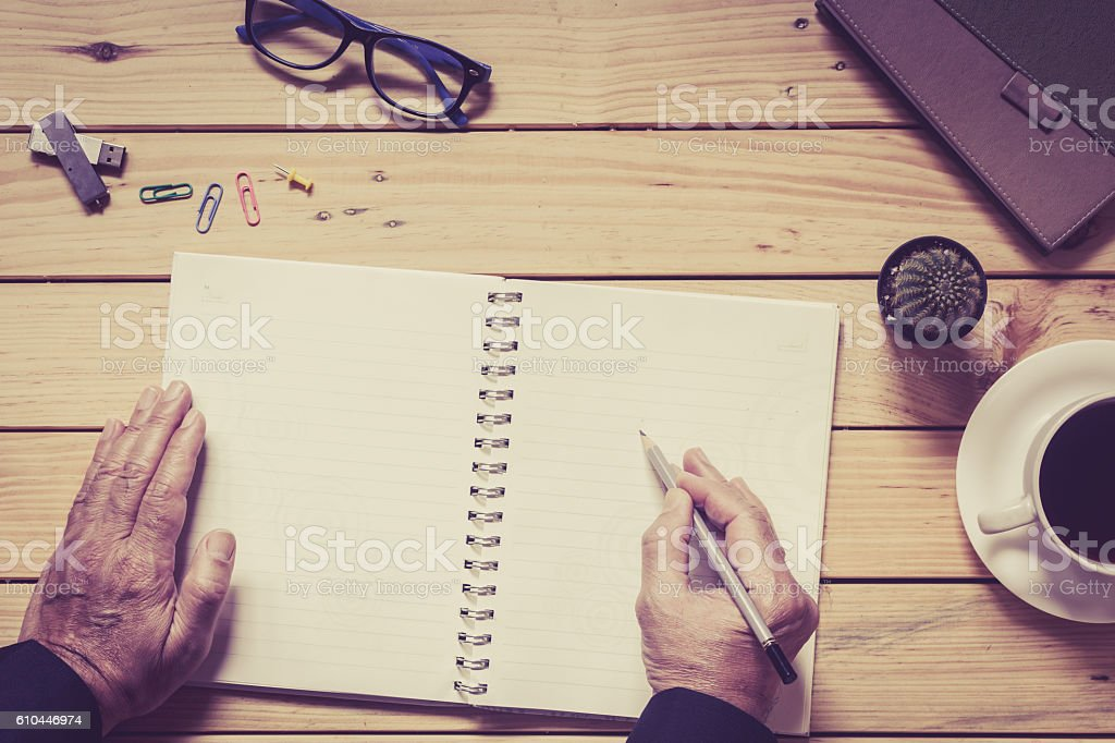 Hans writing on a wooden table with office supplies stock photo
