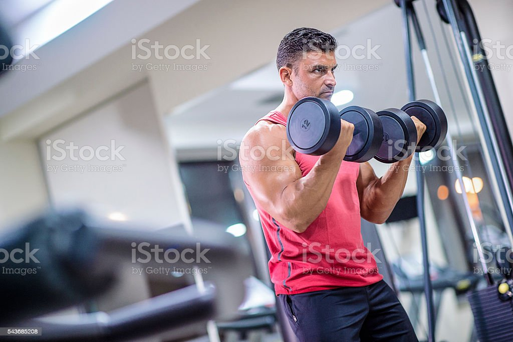 Hansome athletic guy working with dumbbells stock photo