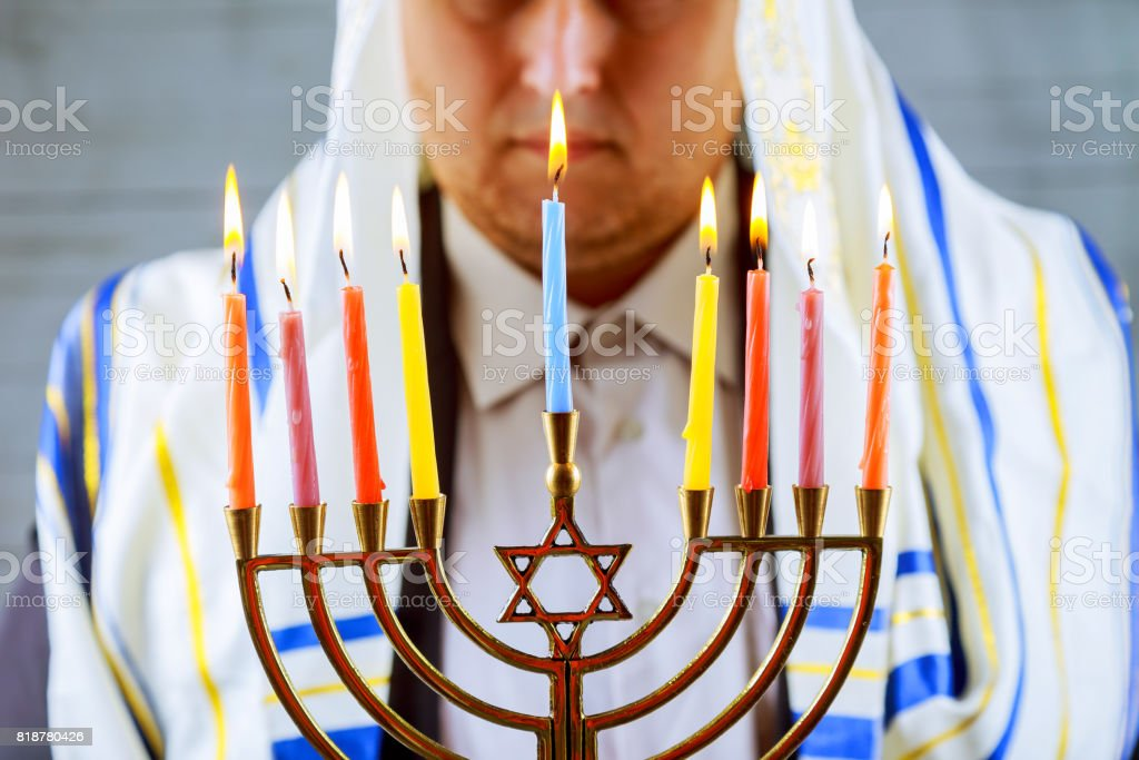 Hanukkah, a Jewish celebration. Candles burning in the menorah, man in the background. stock photo