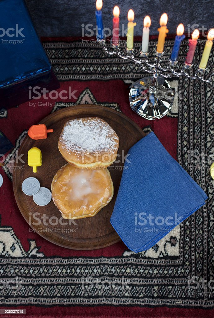 Hanukkah Menorah with lit Candles, Gifts, Dreidel and Jelly Fill stock photo