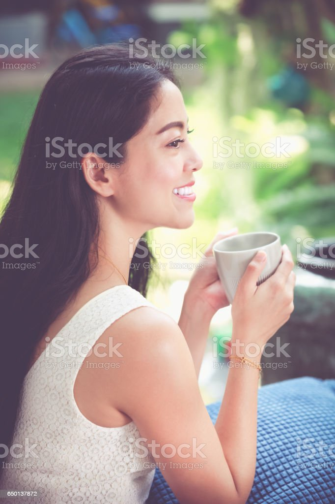 Happily asian woman enjoys fresh coffee in the morning. stock photo
