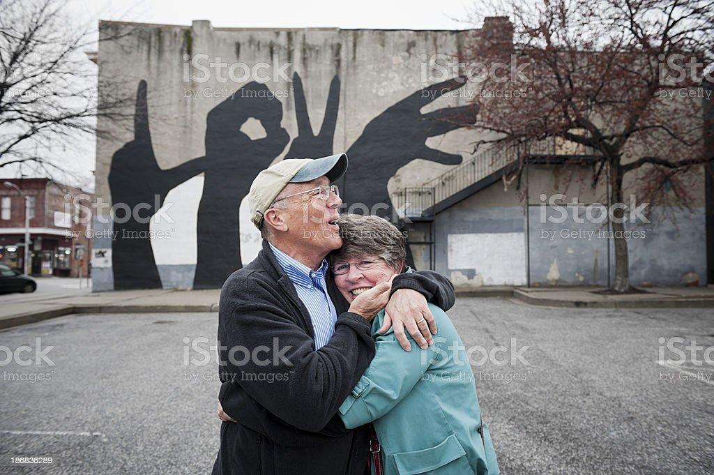 Happily Married Seniors in Front of Love Wall royalty-free stock photo