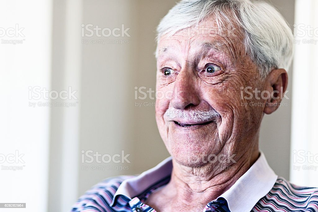 Happily surprised old man smiles stock photo