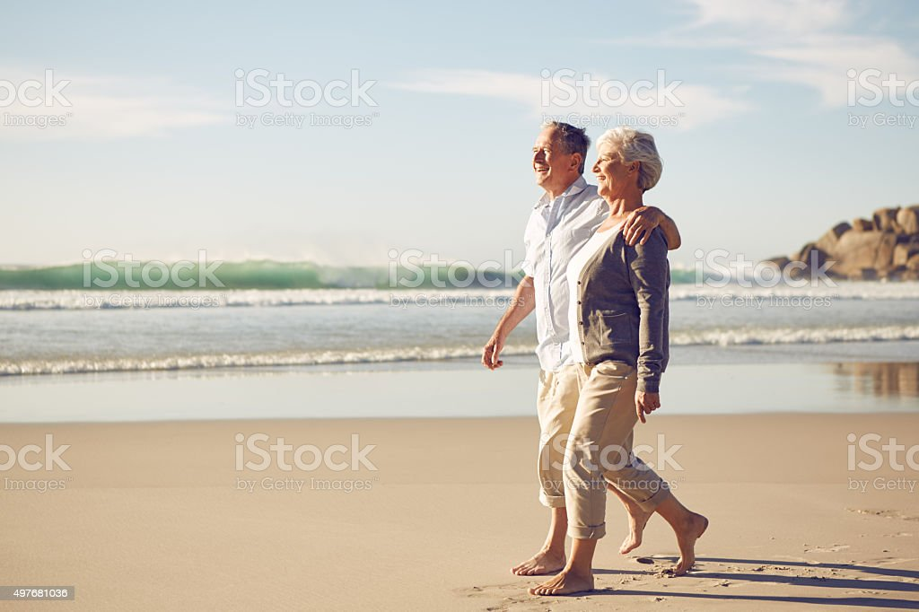 Happily walking along the beach stock photo