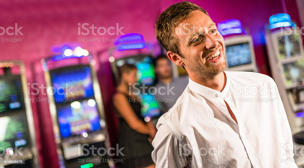 happiness casino owner standing in front of slot machines stock photo