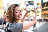 happiness japanese woman taking picture on shibuya