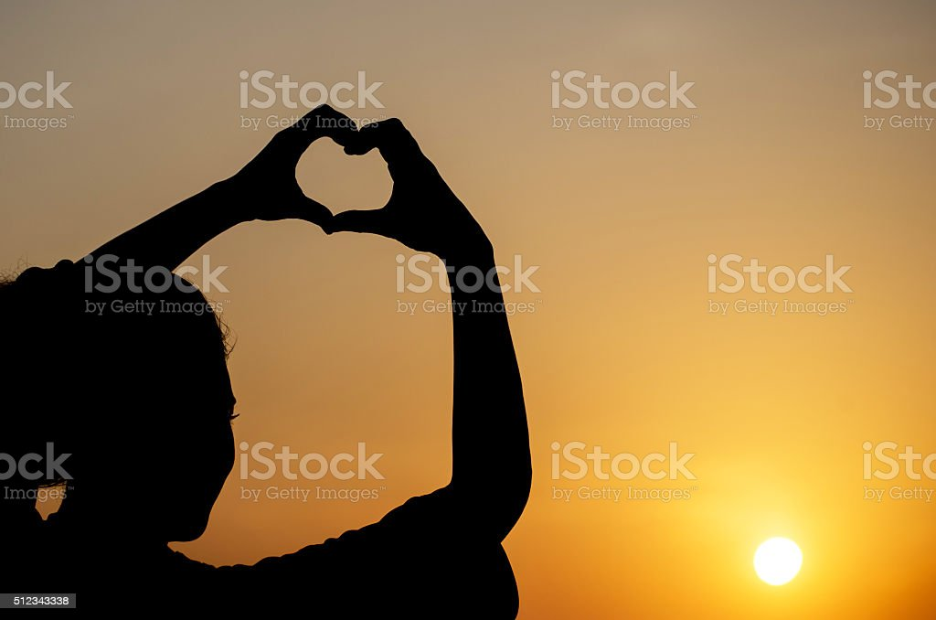 happiness silhouette woman making heart shape stock photo