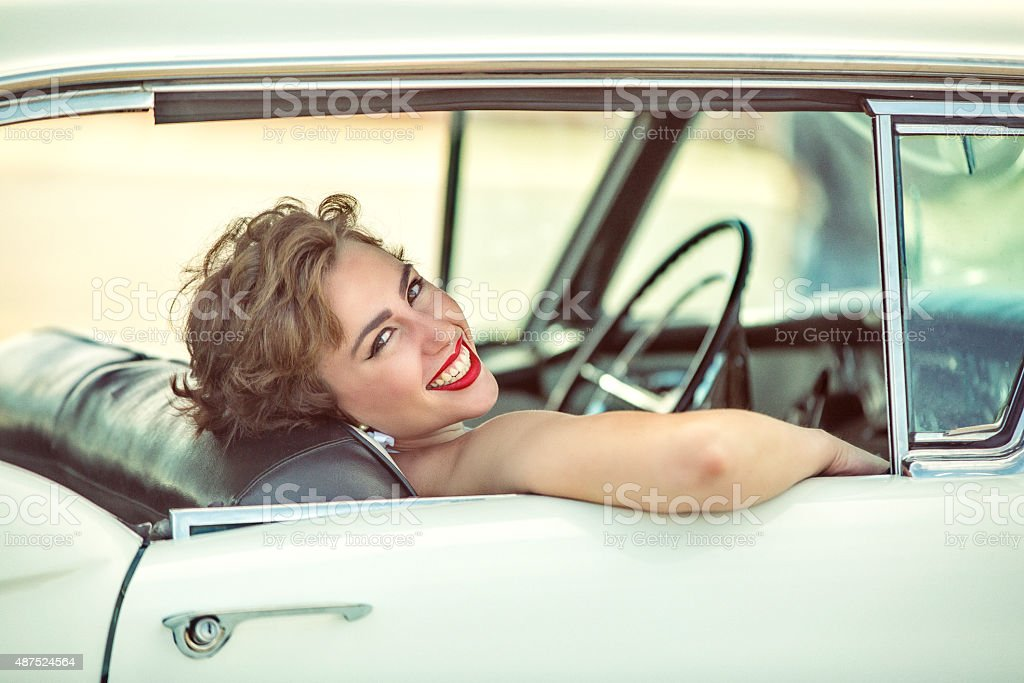 Happy 1950s  Woman Smiling and Lauging in a Vintage Car stock photo