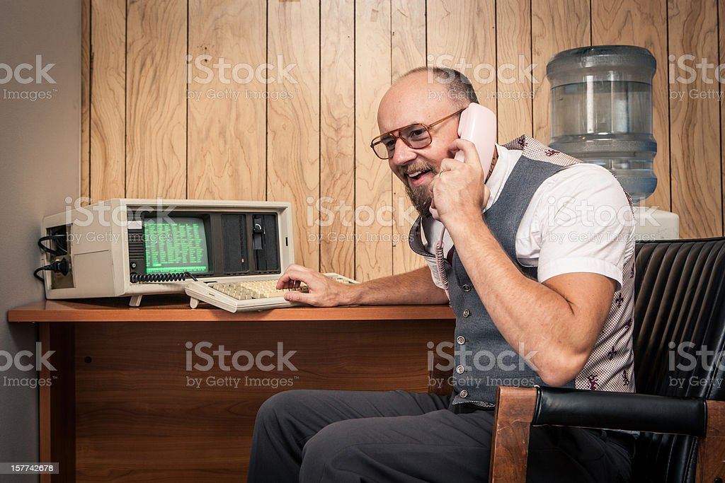 Happy 1980's computer worker nerd  on phone at cubicle royalty-free stock photo
