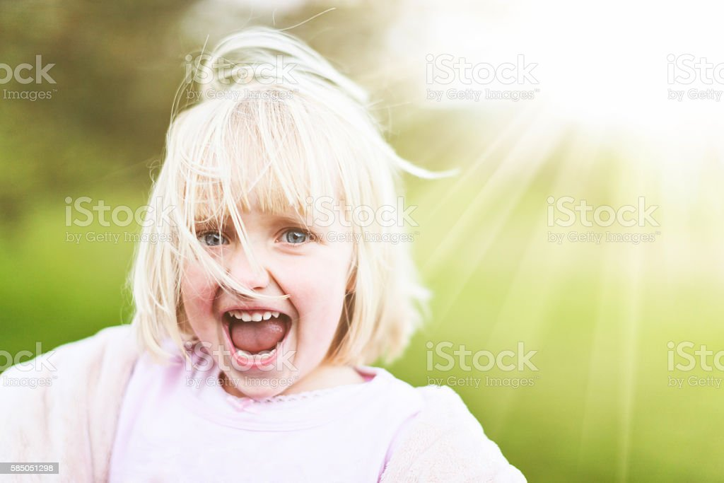 Happy 3-year-old girl dancing in the sunshine, hair flying stock photo