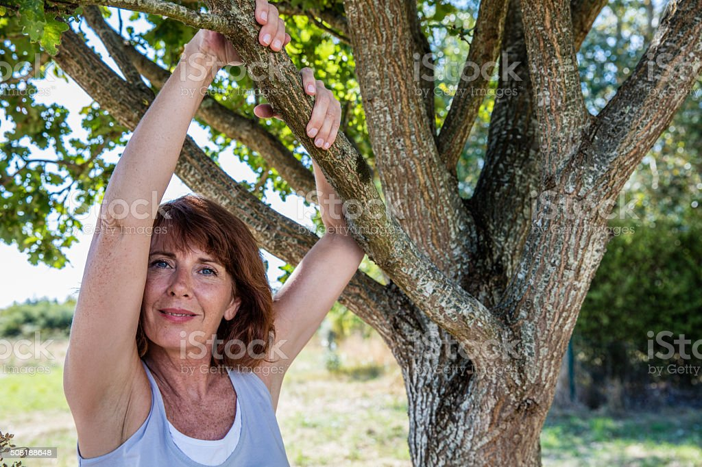 happy 50s woman under a tree for metaphor of serenity stock photo