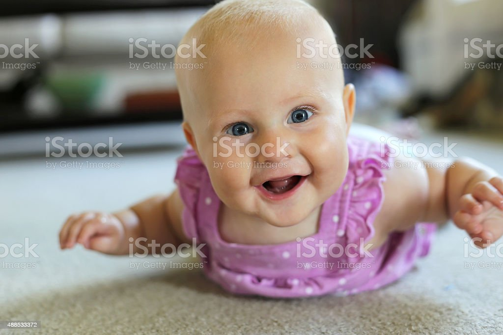Happy 6 Month old Baby Girl Learning to Crawl stock photo