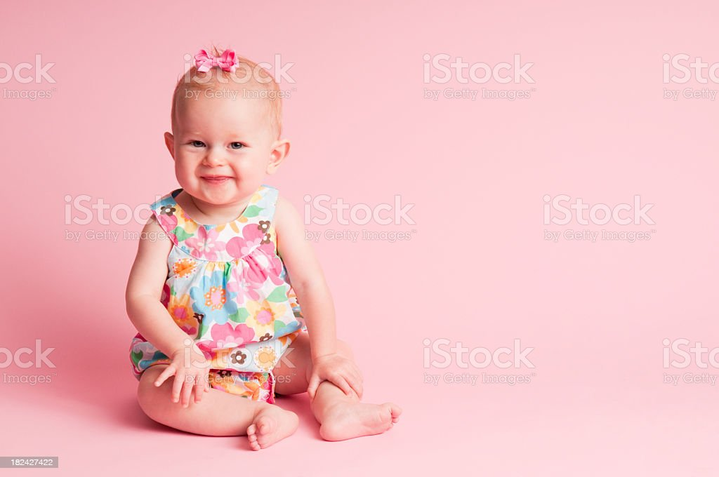 Happy 9-Month-Old Baby Girl Sitting on Pink Background stock photo