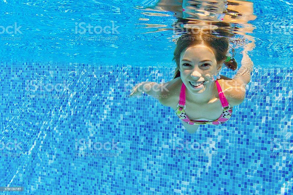 Happy active girl swims underwater in pool stock photo
