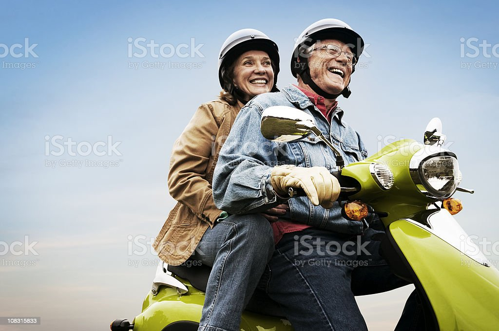 Happy Active Senior Couple on Scooter stock photo
