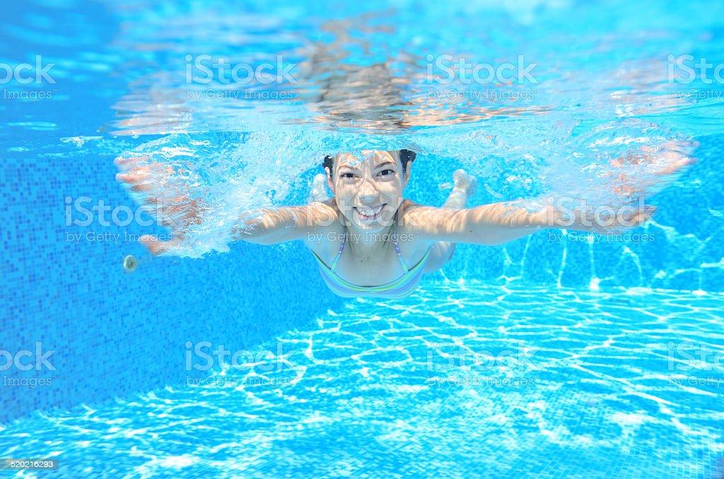 Happy active underwater child swims in pool stock photo